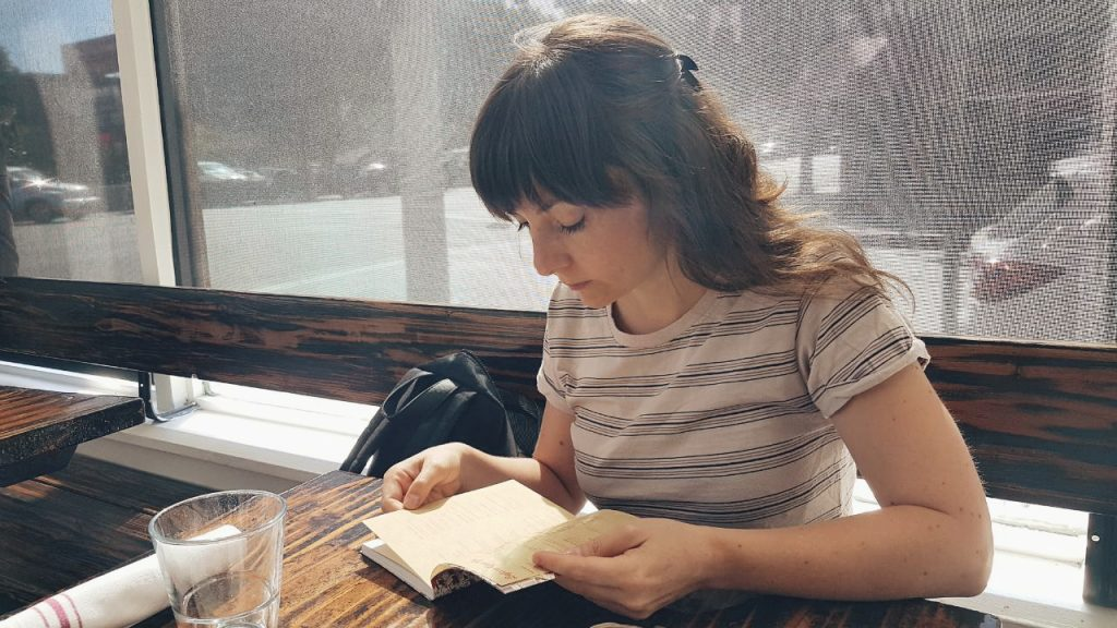 monica galan reading in a cafeteria in LA