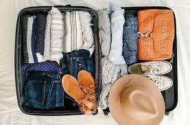 Maleta organizada con la ropa bien doblada, sandalias y sombrero.